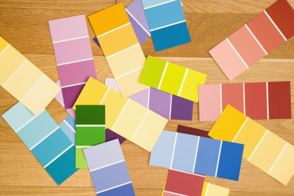 Paint color swatches spread out on wood floor.